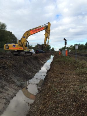 Digger working on drainage infrastructure following a railway