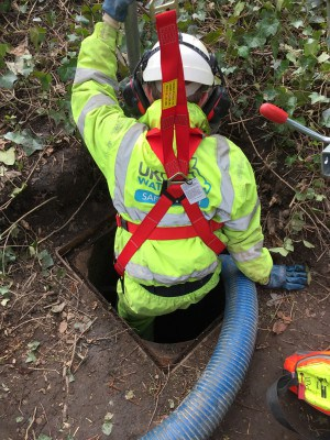 Worker in high-vis going down a man hole