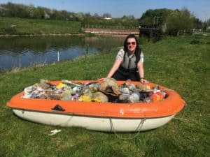 Sian fishes out plastic from river