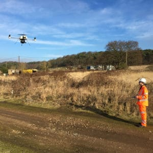 Surveying quadcopter hovering above the ground next to operator