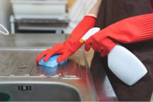 Gloved hands cleaning a steel sink