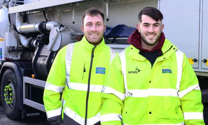 Two Severn Trent workers in day glow high visibility jackets, smiling