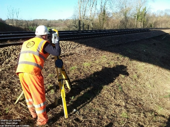 UKDN railway worker using a total station at the side of a railroad track
